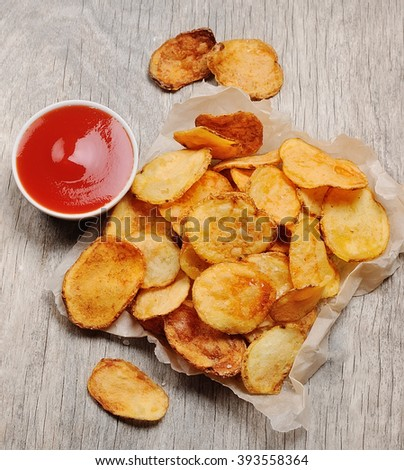 Homemade chips with tomatoes sauce on wooden backgrounds . Potato chips - stock photo