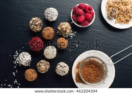 Homemade chocolate and nuts candy balls with cocoa powder, coconut, berries and chopped hazelnuts on black stone background, top view