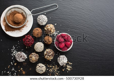 Homemade chocolate and nuts candy balls with cocoa powder, coconut, berries and chopped hazelnuts on black stone background, top view. Healthy Eating concept
