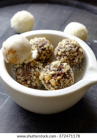 Homemade chocolate and walnut ball sweets in a white ceramic bowl in portrait side