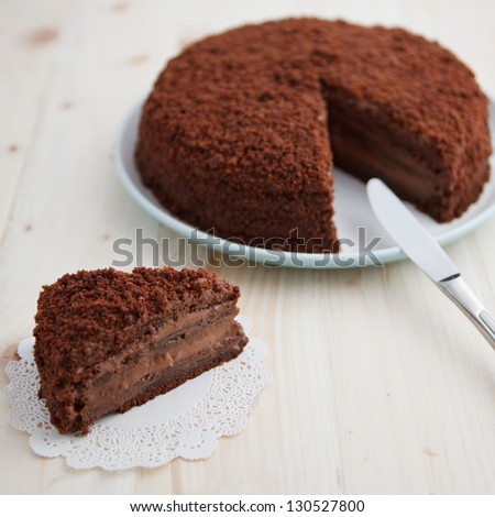 Homemade chocolate blackout cake with a cut piece on a wooden table, square - stock photo
