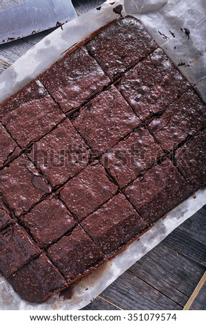 Homemade chocolate brownies cuted by squares on dark wood background woth baking sheet and pan. Top view. - stock photo