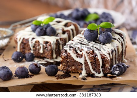 Homemade chocolate brownies with fresh berries and nuts on old rustic wooden background, selective focus - stock photo
