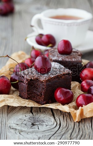 Homemade chocolate brownies with fresh berry and cup of tea on rustic old wooden background, selective focus - stock photo