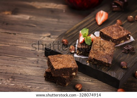 Homemade chocolate brownies with hazelnuts on grunge brown wooden table. Toned image. Selective focus - stock photo
