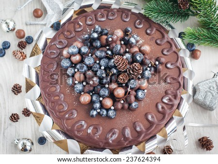 Homemade chocolate cake (Bird`s milk) with fresh berries and christmas decoration - stock photo