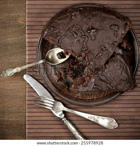 Homemade chocolate cake in plate with silverware on brown wood. Top view point. - stock photo