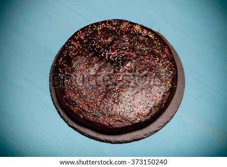 Homemade chocolate cake on blue wooden background. Toned.