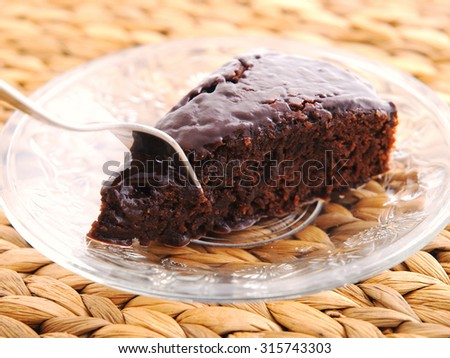 Homemade chocolate cake, one piece in a glass plate
