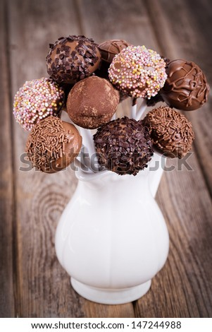 Homemade chocolate cake pops in a white jug. Vintage effect on old wood table. - stock photo