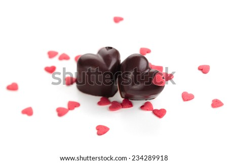 Homemade chocolate candies decorated with heart shaped sprinkles. Isolated on white background. - stock photo