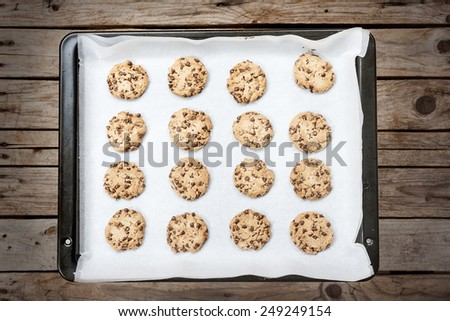 Homemade chocolate chip cookie just baked on a tray over wooden background - stock photo