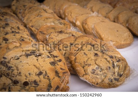 Homemade chocolate chip cookies wrapped in plastic wrap looking yummy with a shallow depth of field. - stock photo