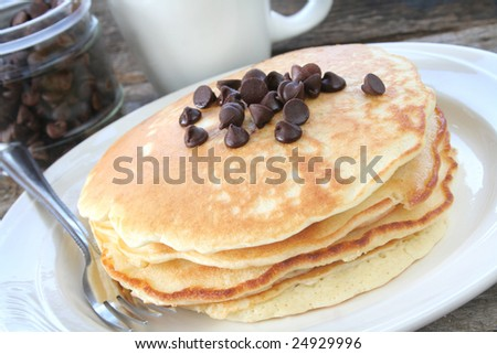 Homemade chocolate chip pancakes on a plate with fork.  Coffee and a dish of chocolate chips in the background. - stock photo
