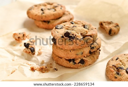 Homemade chocolate chips crispy cookies on baking paper in a morning light - stock photo