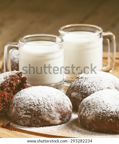 Homemade chocolate cookies sprinkled with powdered sugar and milk in old-fashioned vintage mugs, selective focus