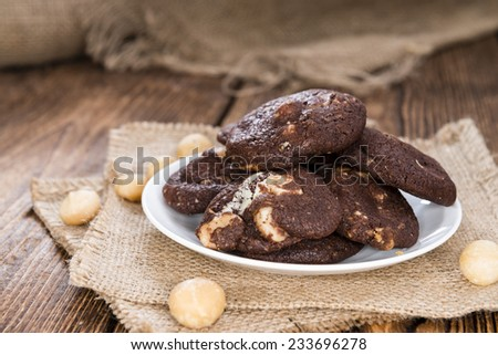 Homemade chocolate Cookies (with macadamia nuts) on wooden background - stock photo