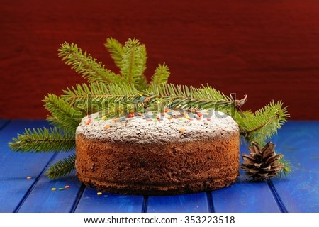 Homemade chocolate fruit christmas cake with green fur tree branch and cone