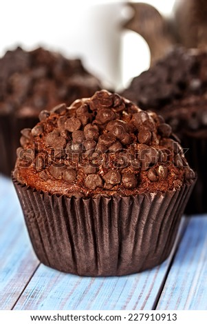 Homemade chocolate muffins in paper cupcake holder on a wooden background