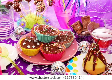 homemade chocolate muffins with colorful topping and other sweets on birthday party table for child - stock photo