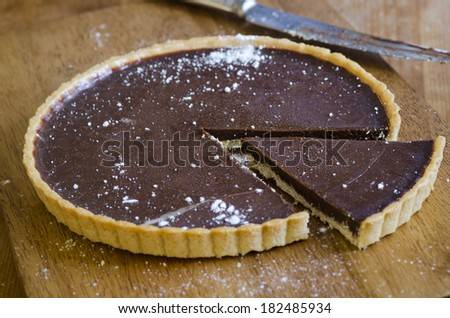 Homemade chocolate tart on a wooden board - stock photo