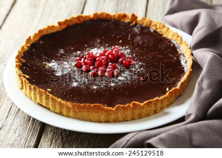 Homemade chocolate tart with pomegranate on grey wooden background - stock photo