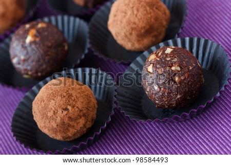 Homemade chocolate truffle on a lilac background.