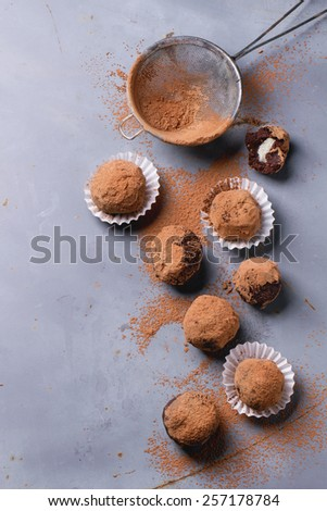 Homemade chocolate truffles with marzipan and cocoa powder over gray matal surface. Top view. - stock photo
