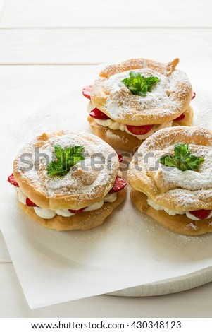 Homemade choux pastry rings with cottage cheese cream and strawberries decorated mint leaves on white wooden background