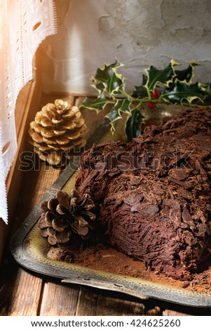 Homemade christmas chocolate yule log on vintage tray with cones and holly branch over wooden window sill in day light. Rustic style. - stock photo