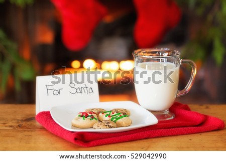 Homemade Christmas cookies and milk with a note for Santa in front of a fireplace with stockings