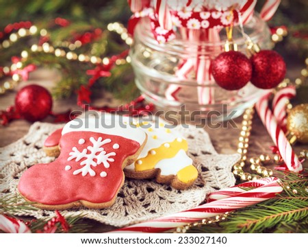 Homemade christmas gingerbreads  and red candy canes in the glass jar between Christmas decorations on wooden table, selective focus. Toned - stock photo