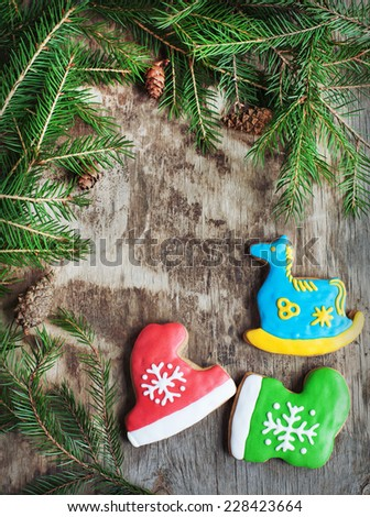 Homemade christmas gingerbreads painted as a blue horse, a red hat and green boot on the wooden background with fir branches. Selective focus and place for text. Toned - stock photo