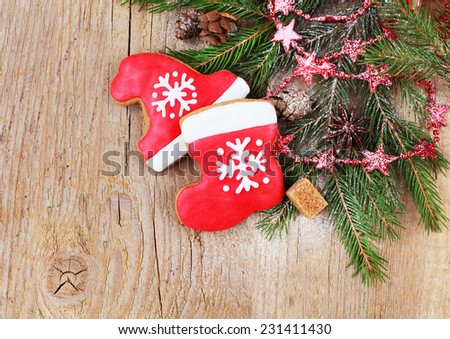 Homemade christmas gingerbreads painted as a red hat and boot of Santa with snowflake with with festive decoration on the wooden background with fir branches . Selective focus and place for text. - stock photo