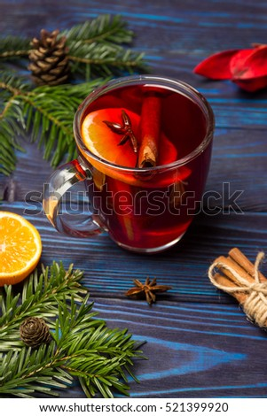 Homemade Christmas mulled wine on a blue wooden background. Christmas composition: tangerine, cinnamon sticks, Christmas tree branch