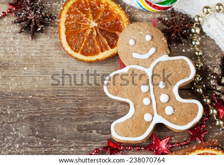 Homemade christmas painted gingerbreads (gingerbread man and red boot) on the wooden background with Christmas decorations and candied orange. Selective focus and place for text. Toned and snow. - stock photo