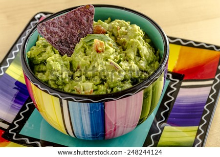 Homemade chunky guacamole in colorful bowl garnished with blue corn tortilla chip and cilantro - stock photo