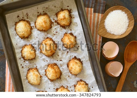 Homemade coconut macaroons (coconut meringue cookies) in baking pan, photographed overhead with natural light. Coconut macaroons are traditional Christmas cookies in Germany called Kokosmakronen.