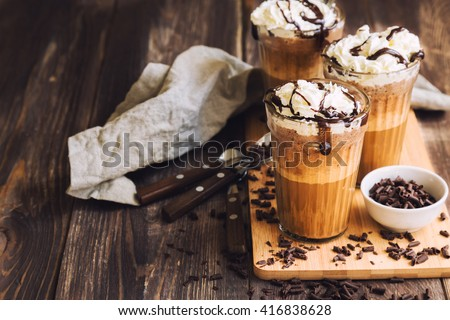 Homemade coffee cocktail with whipped cream and liquid chocolate on rustic wooden background - stock photo