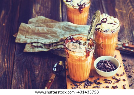 Homemade coffee cocktail with whipped cream and liquid chocolate on rustic wooden background. Vintage toned picture. - stock photo