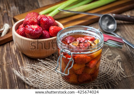 Homemade compote of rhubarb and strawberries on wooden table. - stock photo