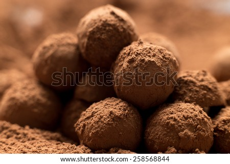 Homemade confectionery. Stack of enticing dark chocolate balls covered in cocoa, close up. Shallow depth of field - stock photo