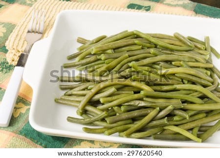 homemade cooked string green beans served in a white casserole dish. There is a fork lying to the side on a stack of yellow kitchen napkins. The background is a Thanksgiving themed tablecloth. - stock photo