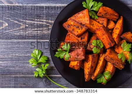 Homemade Cooked Sweet Potato with spices and herbs on dark background. - stock photo