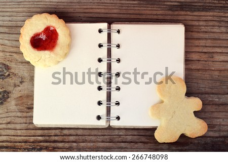 Homemade cookies in shape of man and with heart shaped jam and empty retro spiral recipe book on wooden table - stock photo
