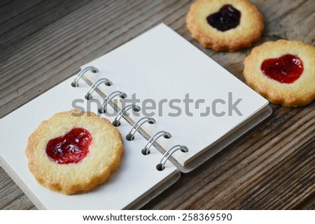 Homemade cookies with heart shaped jam and empty retro spiral recipe book on wooden table - stock photo
