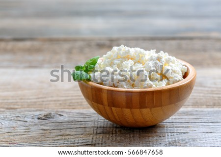 Homemade cottage cheese in a bowl on old wooden table.