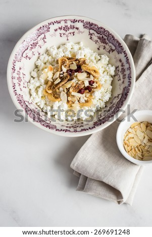 Homemade cottage cheese with dried figs, berries, almond flakes and honey in a bowl for breakfast, selective focus - stock photo