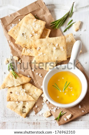Homemade crackers and honey with rosemary and sea salt for appetizer on an old cooking board. - stock photo