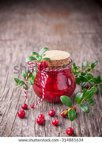 Homemade cranberry sauce in a small jar with cork lid is decorated with sprigs of cranberries with ripe berries on a dark wooden background. selective Focus - stock photo